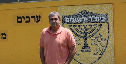 אלי כהן לצד הסמל של בית