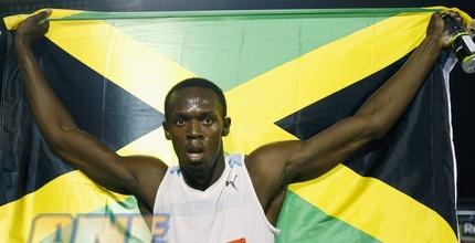 בולט חוגג את הניצחון והשיא עם דגל ג'מייקה (רויטרס)