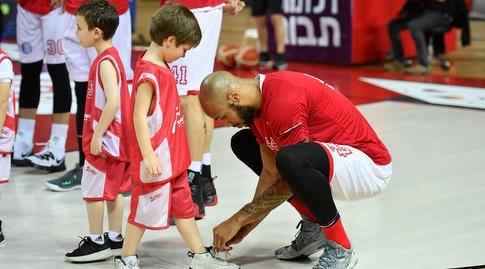 ג'ארלון גרין עוזר לילד המלווה שלו לקשור שרוכים לפני פתיחת המשחק (חגי מיכאלי)