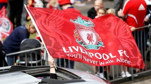 אוהד ליברפול מניף את דגל הקבוצה ממכוניתו (רויטרס)