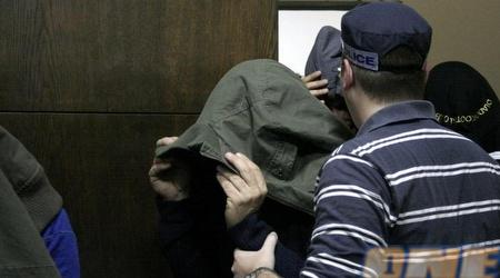 אחד החשודים מכסה את פניו בדיון שנערך בבית המשפט השלום (מתן להב)