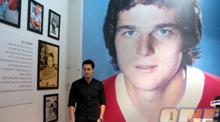 """תמיר כהן על רקע תמונת אביו. """"המשך הקריירה באנגליה יהיה הנצחה"""" (יניב גונן)"""